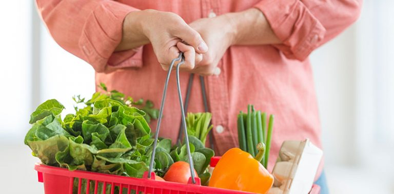 A person is holding a grocery basket with IBS-friendly foods