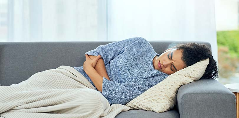 A girl laying on a couch under a blanket, clutching her stomach.